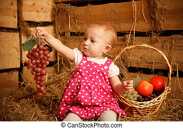 Little girl is sitting on pile of straw with grapes in their hands. Behing fruit basket.