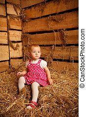 Little girl is sitting on pile of straw in hayloft against...