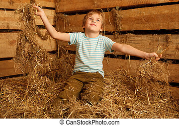 Portrait of boy playing in pile of straw in hayloft....