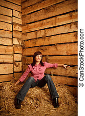 Portrait of girl in red shirt sitting on pile of straw in...