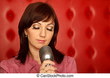 Portrait of girl in red shirt with microphone on rack against red wall. Horizontal format.