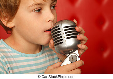 Portrait of boy with microphone in his hands against red wall. ?lose up.