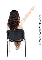 back view of young beautiful woman sitting on chair and...