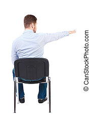back view of young business man sitting on chair and pointing