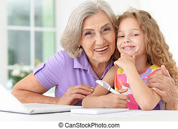 little girl with granny using laptop - Cute little girl in...