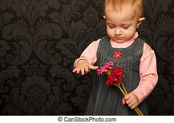 Portrait of a little girl with flowers on a background wall with patterned wallpaper.