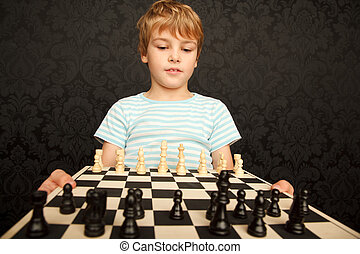 Portrait of boy in T-shirt with chessboard against the wall with ornament.  Horizontal format.