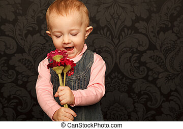 Portrait of little girl with flowers in her hands against ornamental wall.