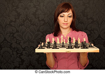 Portrait of girl in red shirt with chessboard against the wall with ornament.  Horizontal format.