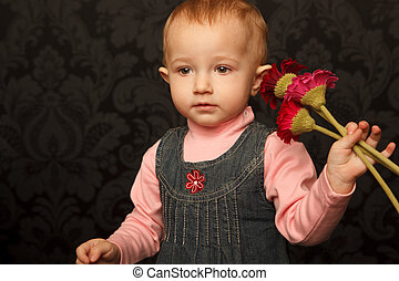 Portrait of little girl with flowers in her hands against ornamental wall. Horizontal format.