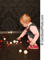 Portrait of little girl with Christmas toys in her hands against ornamental wall.