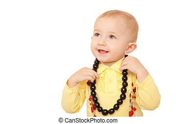 Portrait of little girl in yellow shirt with beads on white background.