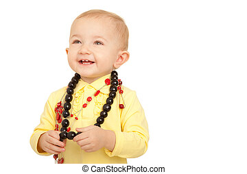 Portrait of smiling little girl in yellow shirt with beads on white background.