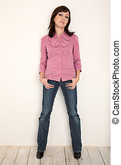 Portrait of girl in red shirt and jeans at full hight against white wall. Vertical format.