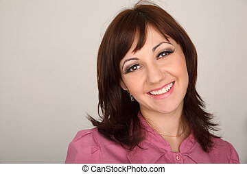 Portrait of smiling girl in red shirt against white wall. Horizontal format.