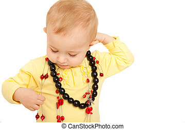 Portrait of little girl eyes set down in yellow shirt with beads on white background.