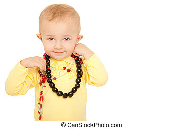 Portrait of smiling little girl looks into camera in yellow shirt with beads on white background.