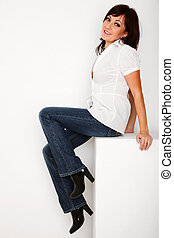 Portrait of girl in jeans and white shirt sitting in white studio. Vertical format.