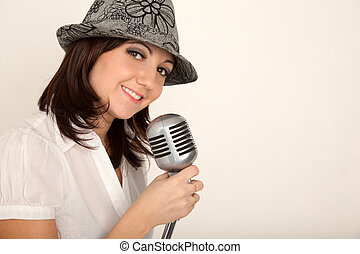 Portrait of girl wearing hat in white shirt with microphone on rack against white wall. Horizontal format.