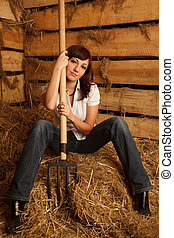 Portrait of girl in white shirt and blue jeans on pile of straw in hayloft. Vertical format.