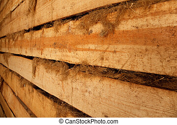 Wall of barn of rough planks with oakum receding into distance. Horizontal format.