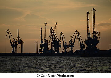 SILHOUETTES OF CRANES AT SUNSET - industrial or portual...