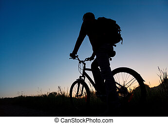 Silhouette of the bicyclist against the dark sky