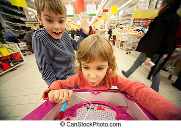 Small girl and boy sit in shoppingcart, play new toy and smile