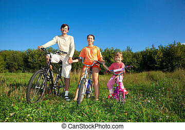 Parents with the daughter on bicycles in park a sunny day. Keep for hands.