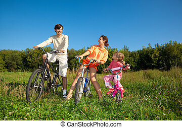 Family from three persons on bicycles in the country. Mum with a daughter look at the daddy.