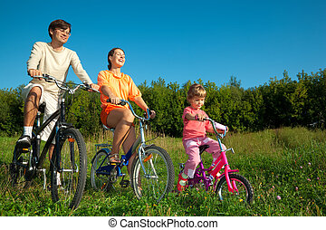 The father, mum and daughter go for a drive a sunny day on bicycles.