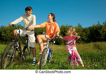 The father, mum and daughter on bicycles in park. To keep the friend for the friend hands.