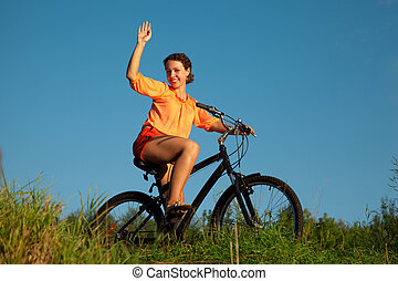 The girl waves a hand sitting on a bicycle