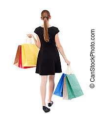 back view of going woman with shopping bags beautiful girl...