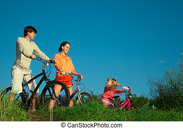 Family from three persons on bicycles. Parents look at a daughter.