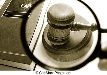 magnifying glass examining a judges court gavel, with law...