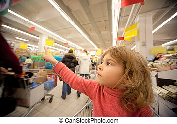 Small girl sit in shoppingcart in supermarket and show by...