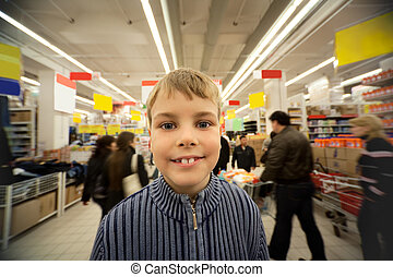Smilling boy stand in centre of trading floor in supermarket