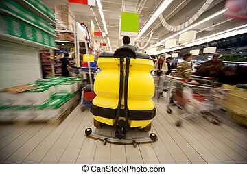 Motion blur of yellow clean machine in centre of trading floor in supermarket