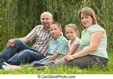 family with two children is sitting at the grass in early fall park