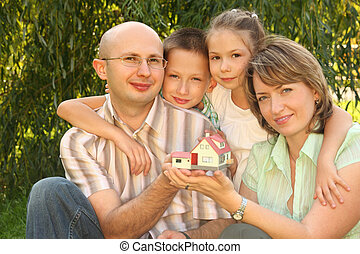 family with two children keeping wendy house in their hands