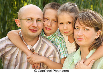 family with two children near osier looking at camera.