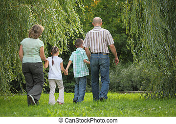 family with two children in early fall park. they are...