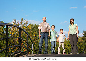 family with two children is standing on bridge and looking at camera.