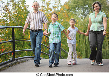 family with two children walking on bridge in early fall park. family is handies. focus on little boy