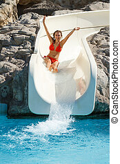 Young adult blond girl sliding a water slide