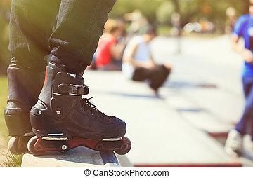 Aggressive inline rollerblader standing on ramp in skatepark...