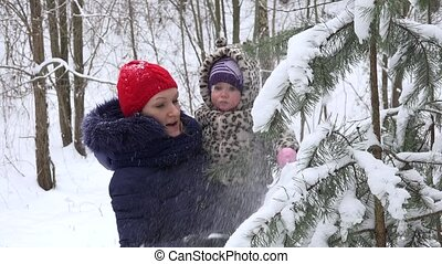mother with baby girl shake off snow from fir tree branches...
