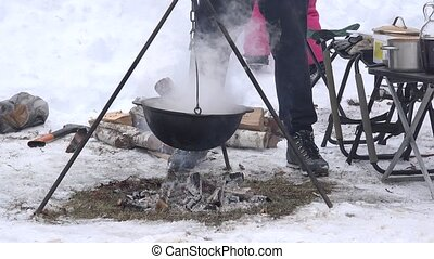 Tourist people cook in pot hanging over campfire fire in winter. 4K