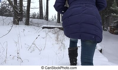 woman climbs up stairs covered with snow in winter park 4K -...